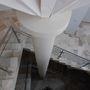 Faszerű tartóoszlop körül tekereg a főlépcső.