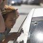 Megdöbbent diákok nézik a golyók ütötte lyukakat az autókon