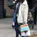 Rachel Weisz suliba viszi a gyereket, mindezt fehér irhakabátban teszi.