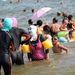 Kínai fürdőzők teljes testet fedő ruhában és arcmaszkban Santung tartomány egyik strandján